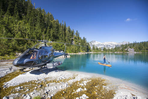Tourist on paddle board next to helicopter during adventure tour. - CAVF77444