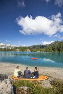 Family relaxing together at remote lake, brother paddling on lake. - CAVF77471