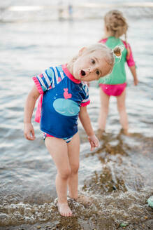 Two toddler girls cooling off at the lake. - CAVF77531