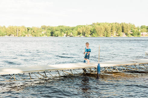 A little boy walking on a boat dock. - CAVF77534