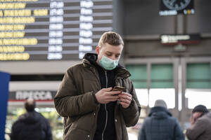 Young man with face mask at train station in the city, using smartphone - VPIF02127