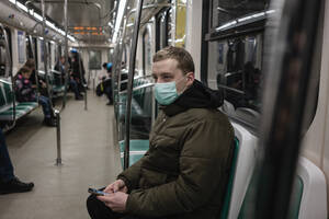 Young man in commuter train, wearing face mask, using smartphone - VPIF02133