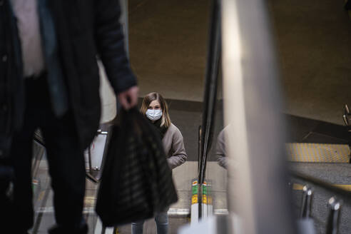 Woman with face mask on escalator at railway station - VPIF02136