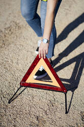 Close-up of woman posting warning triangle - OCMF01074