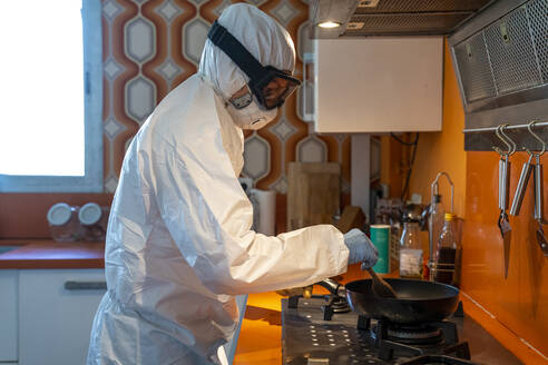 Woman wearing protective clothes, cooking in kitchen - DLTSF00641