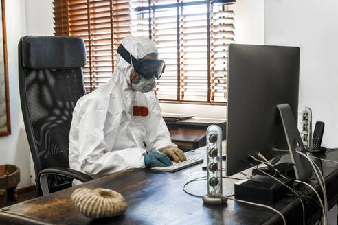 Woman, wearing protective clothes, sitting at desk, using PC - DLTSF00647