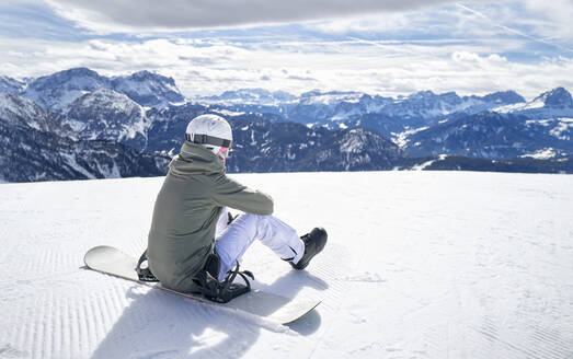 Smiling woman sitting with snowboard on viewpoint and enjoying view at distance - DIKF00375