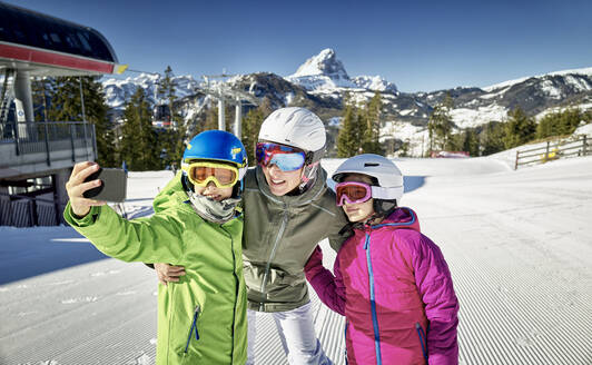Mother with her children, taking a selfie on ski slope - DIKF00387