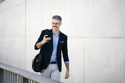Smiling gray-haired businessman walking in the city using cell phone - JRFF04192