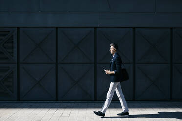 Gray-haired businessman walking along a building in the city - JRFF04210