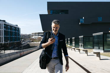 Gray-haired businessman walking with cell phone in the city - JRFF04213