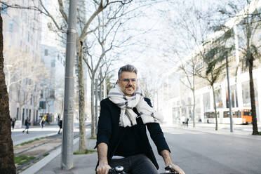 Gray-haired businessman riding bicycle in the city - JRFF04225