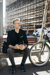 Gray-haired businessman sitting on a bench next to bicycle in the city - JRFF04228