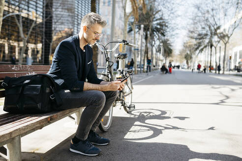 Gray-haired businessman sitting on a bench next to bicycle in the city using cell phone - JRFF04231