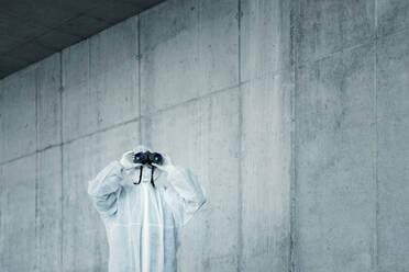 Man wearing protective clothing looking through binoculars - WVF01505