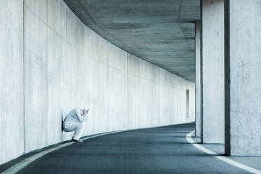Despaired man wearing protective clothing leaning against concrete wall in a tunnel - WVF01508
