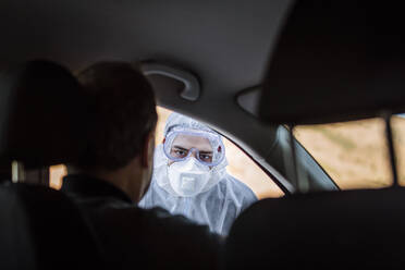 Man wearing protective clothing controlling senior man in car - WVF01523