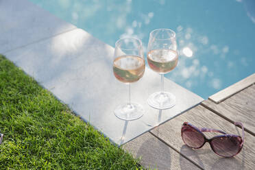 Rose wine and sunglasses at tranquil summer poolside - HOXF05297