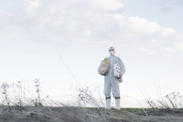Man wearing protective suit and mask holding toilet rolls and grocery bag in the countryside - EYAF00962