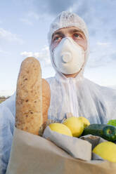 Portrait of man wearing protective suit and mask holding grocery bag outdoors - EYAF00968