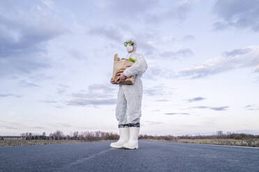 Man wearing protective suit and mask holding grocery bag on a country road - EYAF00971