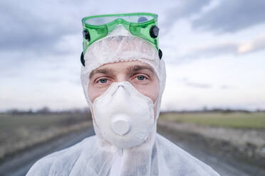 Portrait of man wearing protective suit and mask - EYAF00974