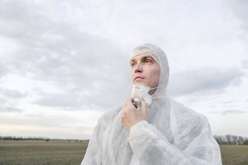 Portrait of man wearing protective suit and mask - EYAF00977