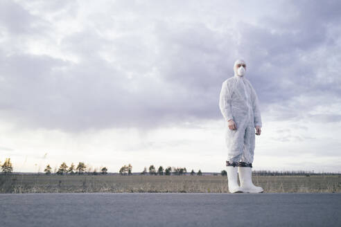 Man wearing protective suit and mask at the roadside of a country road - EYAF00980