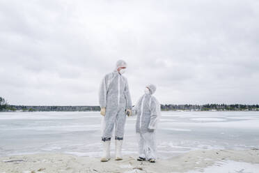 Father and son wearing protective suits standing at frozen river - EYAF00983