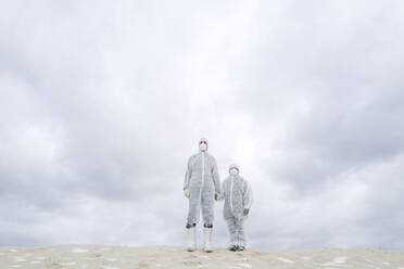 Father and son wearing protective suits standing outdoors in winter - EYAF00989