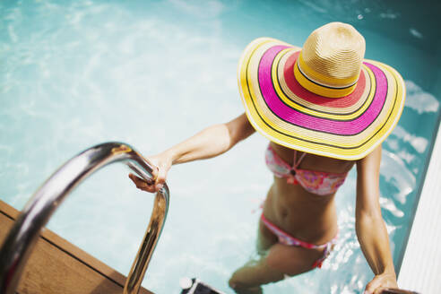 Woman in sun hat and bikini getting out of sunny summer swimming pool - HOXF05471