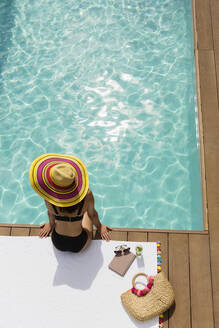 Woman in sun hat and bikini relaxing at sunny poolside - HOXF05483