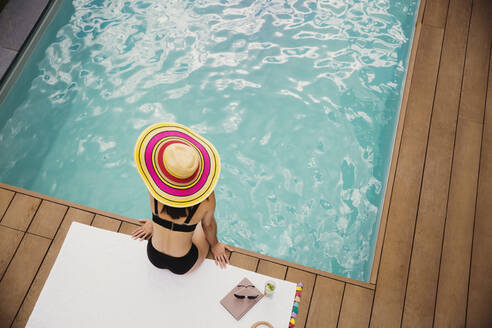 Woman in sun hat and bikini relaxing at poolside - HOXF05495