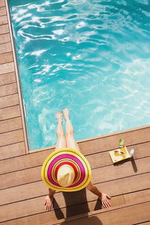 Woman in sun hat relaxing at sunny summer poolside - HOXF05507