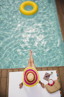 Woman in sun hat relaxing, sunbathing at summer poolside - HOXF05516