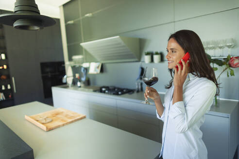 Woman talking on smart phone and drinking red wine in modern kitchen - HOXF05579