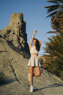 Portrait of fashionable young woman standing on a rock enjoying sunset - MPPF00657