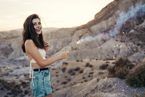 Portrait of happy young woman with sparkler at sunset, Almeria, Spain - MPPF00663