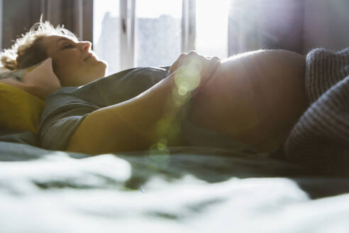 Pregnant woman lying on bed at home - MFF05095