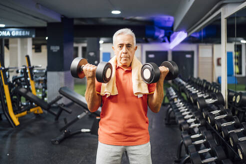 Portrait of senior man lifting dumbbells in gym - OCMF01110