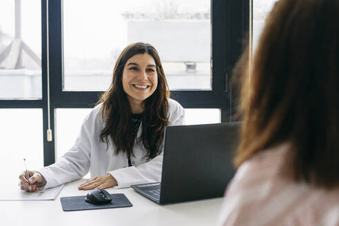 Smiling doctor talking to patient in medical practice - ABZF02995