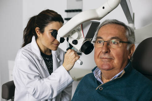 ENT physician examining ear of a senior man - ABZF03028