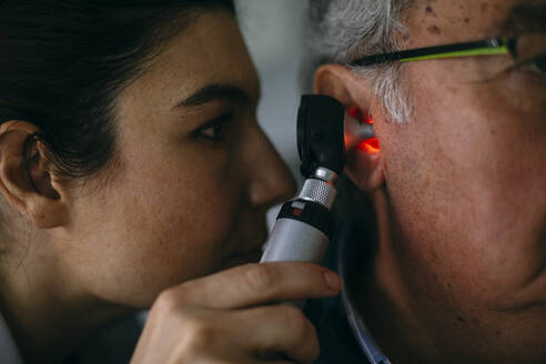 ENT physician examining ear of a senior man with an otoscope - ABZF03031