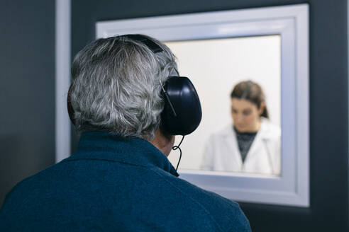 Doctor giving instructions to patient during a hearing test - ABZF03037