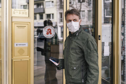 Man with mask waiting in front of pharmacy holding prescription - MFF05131