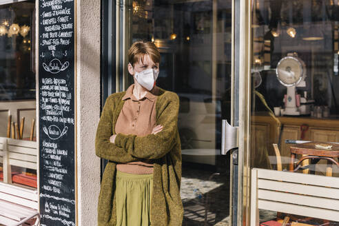Woman wearing mask standing in front of her closed restaurant - MFF05146