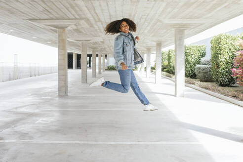Smiling woman jumping in empty parking deck - TCEF00308
