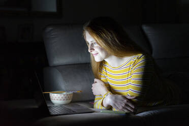 Young woman having a laptop video conference on the couch at home - AFVF05781