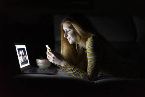 Young woman lying on the couch at home using laptop and smartphone - AFVF05790