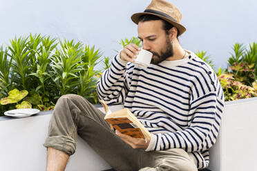 Man sitting on balcony drinking coffee and reading a book - AFVF05798
